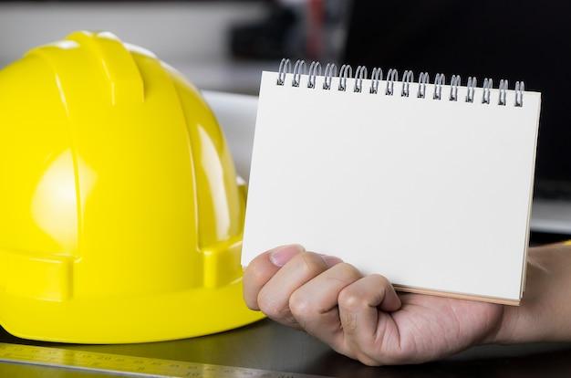 Architetto, muratori, mano dell'ingegnere che tiene la pagina del libro in bianco.
