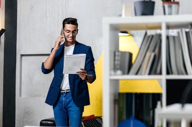 Architetto vestito con abiti eleganti che parla al telefono in una stanza con interni eleganti con scaffali per libri.