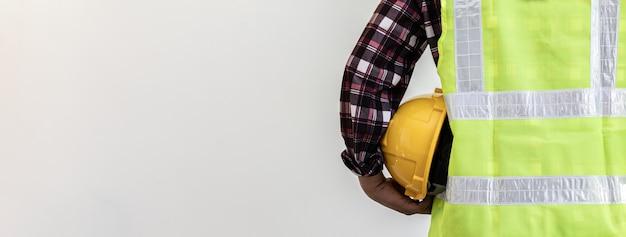 Dietro l'architetto-ingegnere in piedi con la schiena in mano un casco di sicurezza giallo e indossa una tuta riflettente, è vestito per lavorare in un cantiere. concetto di abbigliamento protettivo da costruzione.