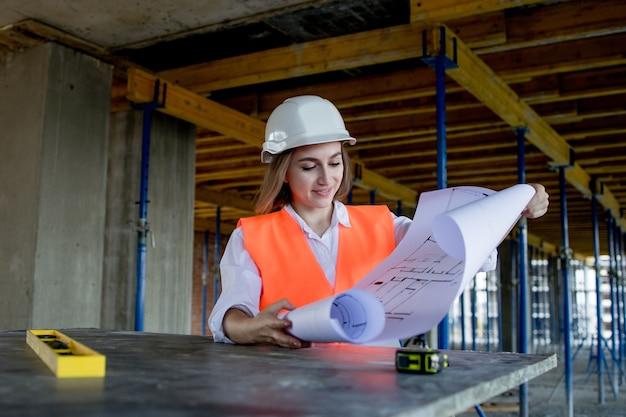 Architetto o ingegnere che lavora, sfogliando il progetto di costruzione all'interno del cantiere con un piano di progetto.