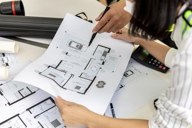 Gli ingegneri architetti sono in attesa di guardare i progetti delle case progettate, si incontrano per pianificare la costruzione e modificare alcuni dei progetti. idee di design e interior design.