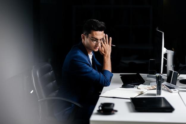 L'architetto con gli occhiali vestito con una giacca blu si siede alla scrivania davanti al computer e pensa.