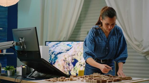 Architetto che tiene maquette in mano utilizzando un computer touch screen