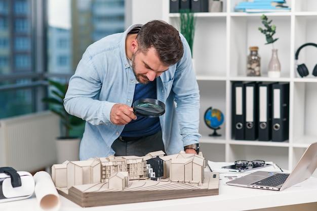 L'ispettore maschio dell'architetto esamina un modello della casa usando una lente d'ingrandimento. ispezione della casa e concetto di bene immobile.