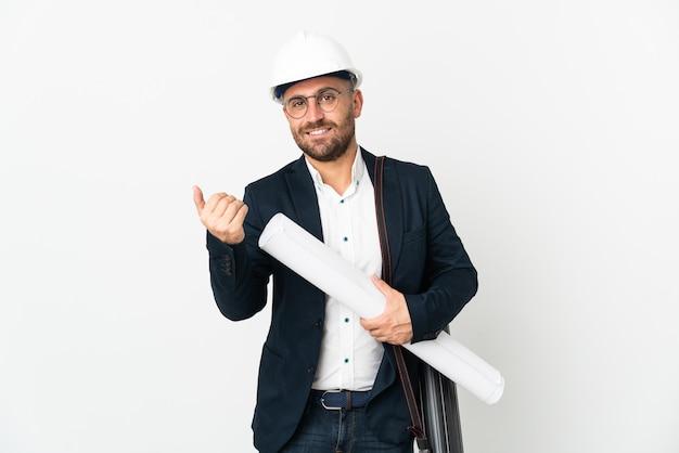 Uomo dell'architetto con il casco e che tiene i modelli isolati su fondo bianco che invita a venire con la mano. felice che tu sia venuto