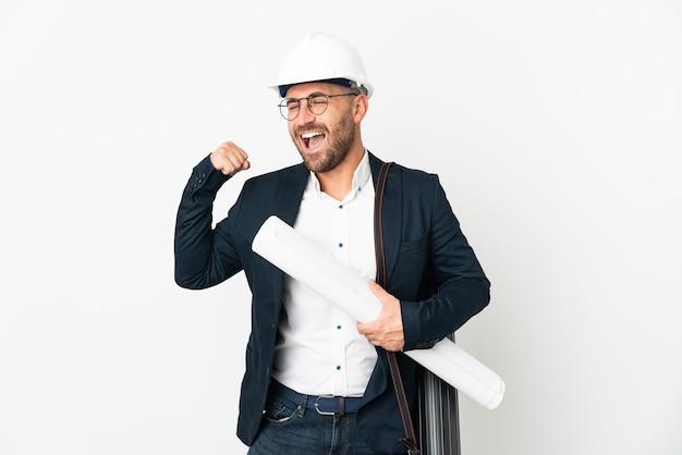 Uomo dell'architetto con il casco e che tiene le cianografie isolate sulla parete bianca che celebra una vittoria