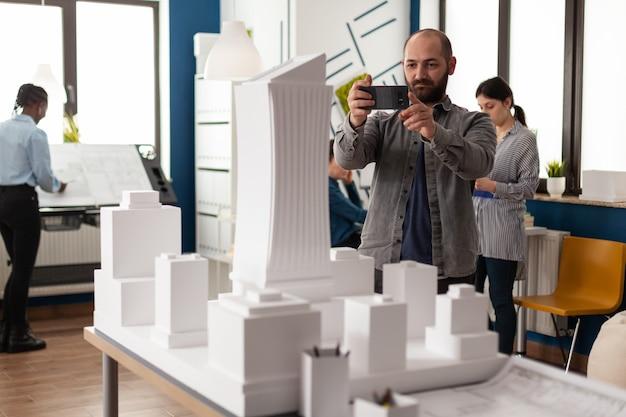 Uomo di professione di architetto che guarda il layout della maquette