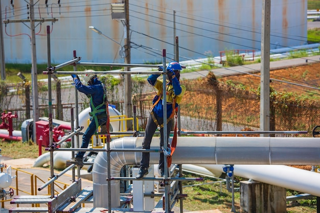 Architetto in cantiere lavoratori edili su una conduttura impalcatura. ampia impalcatura che fornisce piattaforme per lavori in corso. uomini che camminano sul tetto circondati da impalcature