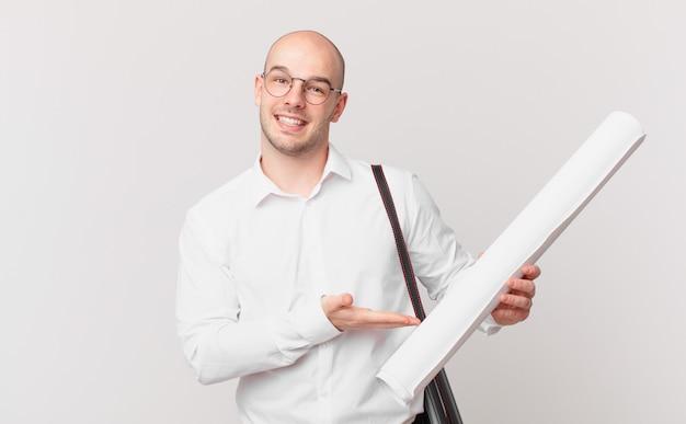 Architetto che sorride allegramente, si sente felice e mostra un concetto nello spazio della copia con il palmo della mano