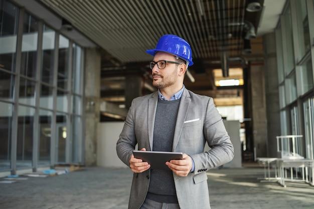 Architetto in piedi nella costruzione nel processo di costruzione e controllo sui lavori