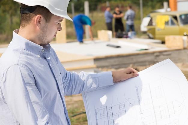 Architetto in piedi che studia un progetto portatile su un cantiere di una nuova casa di costruzione