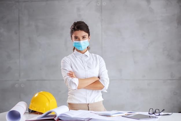 Architetto in piedi con le braccia incrociate durante il coronavirus