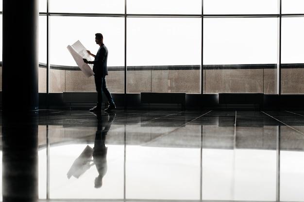 Architetto in abiti eleganti tiene un foglio con un disegno in mano e parla al telefono sullo sfondo di un moderno edificio a più piani in vetro.