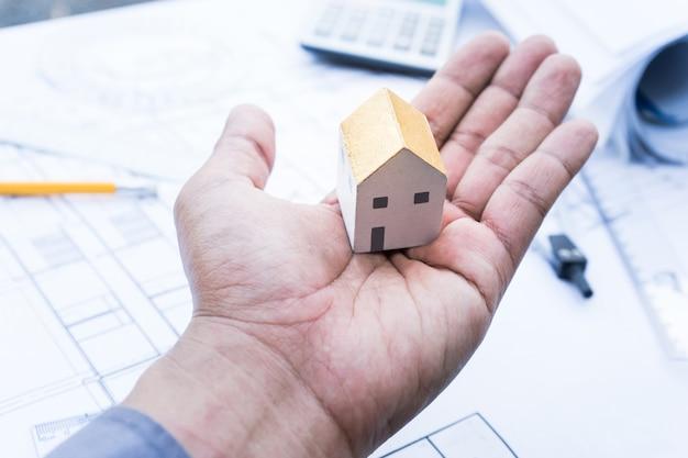 Architetto con piccolo modello di casa a portata di mano e progetto del piano