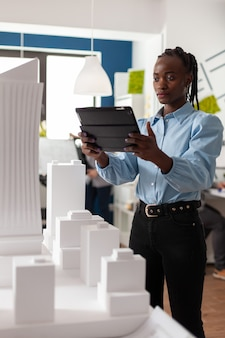 Architetto donna di etnia afroamericana che lavora su tablet guardando maquette professionale bui...