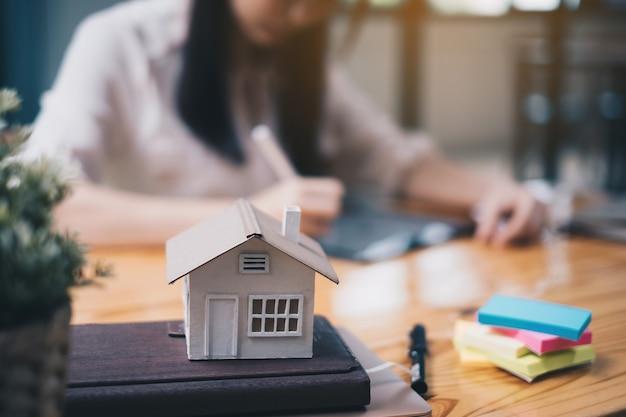 Donna architetto che utilizza un'applicazione per tablet digitale per disegnare a mano una casa di design con un modello su una scrivania di legno. idea di proprietà nel settore immobiliare.