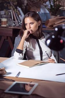 Donna dell'architetto che lavora al tavolo da disegno in ufficio oa casa. tiro
