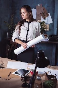 Donna dell'architetto che lavora al tavolo da disegno in ufficio oa casa. foto in studio studio