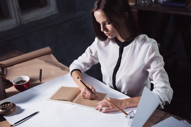 Architetto donna che lavora sul tavolo da disegno in ufficio oa casa