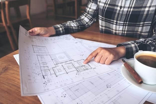 Un architetto che lavora e che punta alla carta da disegno del negozio sul tavolo