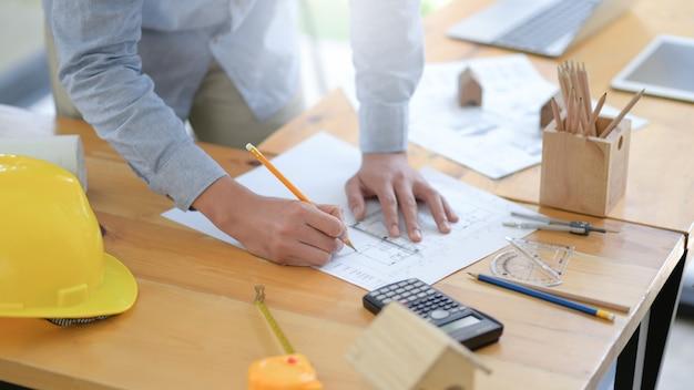 Gli architetti stanno redigendo un piano di casa per presentare i clienti in un ufficio moderno.