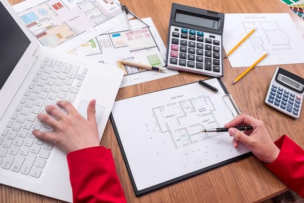Mani di architetti con piano casa, calcolatrice e laptop