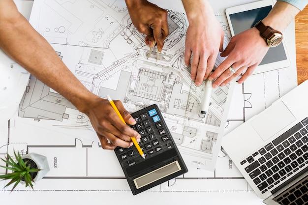 Gli architetti che lavorano sul piano architettonico utilizzando la calcolatrice