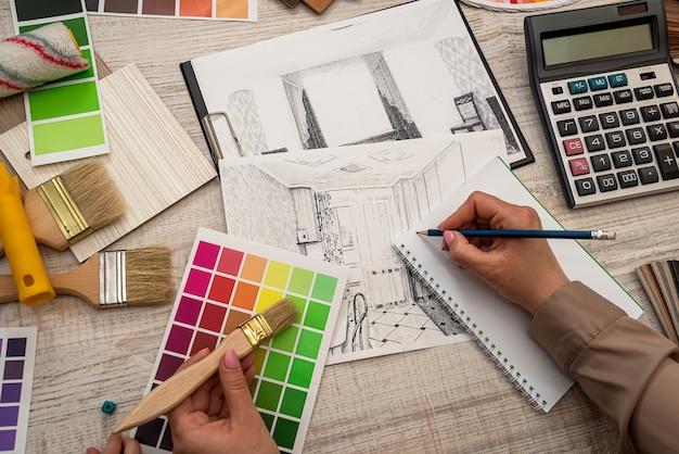 Il progettista architettonico lavora con la tavolozza dei colori e la stampa blu del piano di schizzo Foto Premium