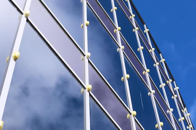 Particolare architettonico della facciata con riflessi multipli di altri edifici e del sole. esterno di un edificio moderno. sfondo astratto di architettura