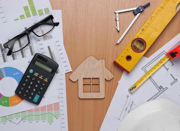 Piano di progetto architettonico, statistiche e grafici. strumenti di ingegneria e forniture per ufficio sul tavolo, area di lavoro. concetto di costruzione di una casa