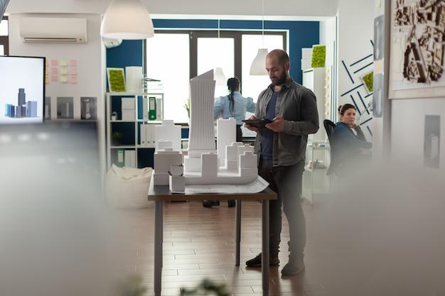 Uomo d'affari di architettura che lavora al tablet in ufficio