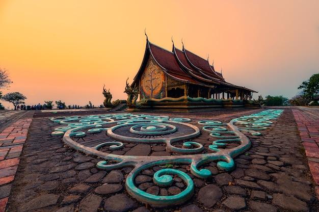 Architettura del tempio della chiesa con albero della bodhi incandescente e pittura fluorescente sul pavimento la sera al wat sirindhorn wararam o wat phu prao a ubon ratchathani, thailandia