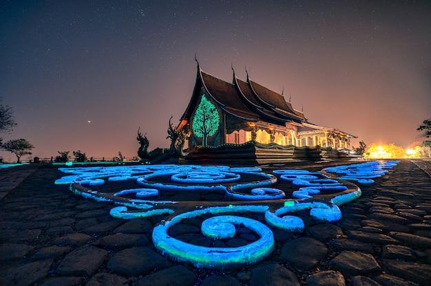 Architettura del tempio della chiesa con bodhi tree incandescente e pittura a fluorescenza sul pavimento al wat sirindhorn wararam o wat phu prao a ubon ratchathani