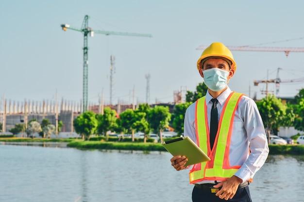 Il tablet dell'ingegnere dell'architettura lavora duramente nella costruzione del sito, festa del lavoro