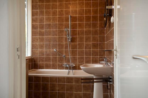 Interni di architettura di un vecchio bagno vintage con piastrelle marroni design antico concetto di casa interna
