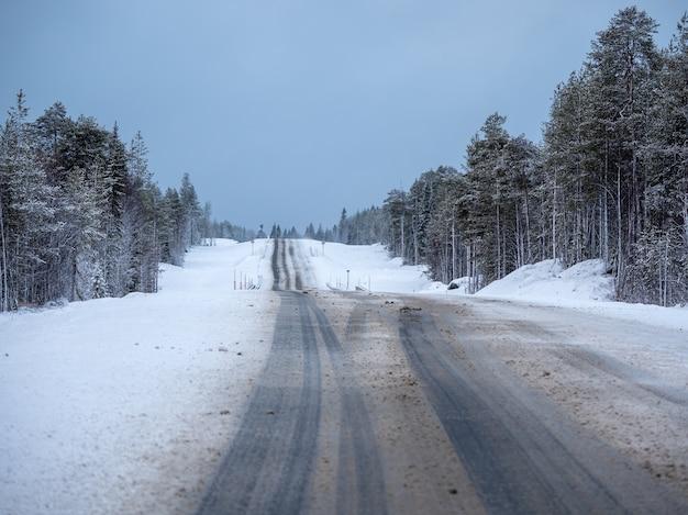 Strada diritta invernale della neve artica attraverso le colline.