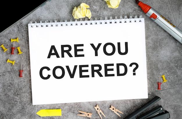 Hai del testo coperto su un quaderno bianco con puntine, pennarello e cucitrice su un tavolo di cemento?