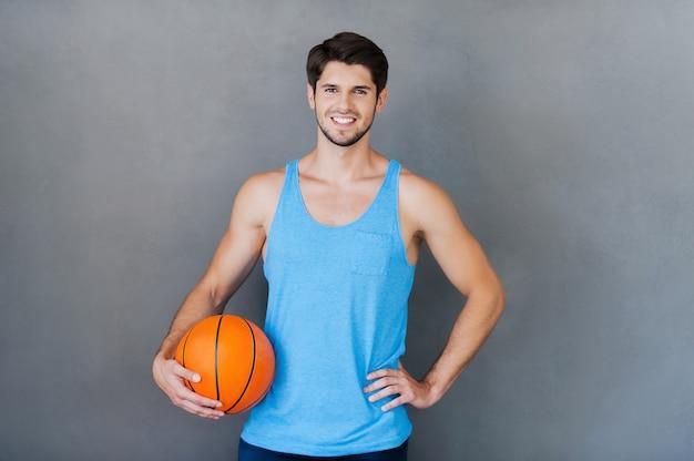 Sei pronto per il gioco? felice giovane uomo muscoloso che tiene la palla da basket mentre si trova su sfondi grigi