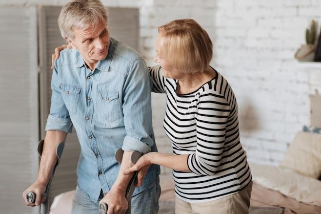 Sei ancora stanco. uomo anziano dedicato luminoso che si riprende da un infortunio alla gamba e usa le stampelle per camminare mentre la sua signora lo incoraggia