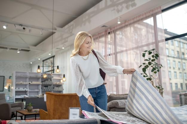 Tappeti. donna in una camicia e jeans guardando piccoli tappeti con motivi, di buon umore.