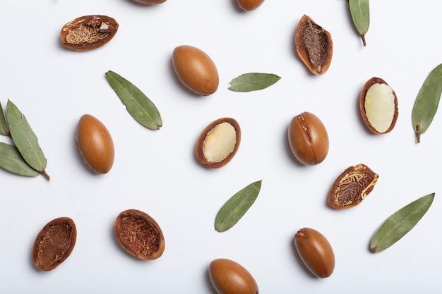 Semi di argan isolati su uno sfondo bianco noci di olio di argan con cosmetici vegetali e oli naturali