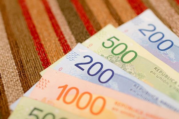 Banconote di denaro argentino su superficie multicolore