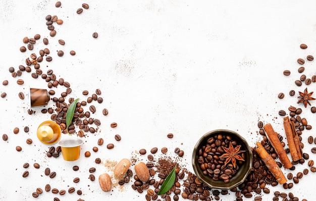 Caffè arioso, chicchi di caffè tostati scuri, macinato e capsule con palette montate su cemento bianco