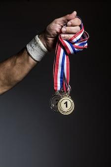 Braccio di atleta anziano che tiene tre medaglie d'oro, d'argento e di bronzo su uno sfondo scuro. sport e concetto di vittoria.