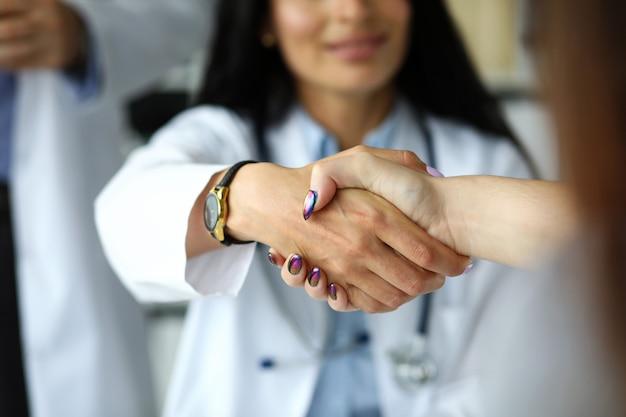 Braccio del gp femminile che stringe le mani con il primo piano dell'ospite. incoraggiamento di auto-introduzione o soluzione di un problema