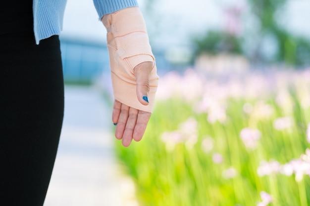 Stecca del braccio, mano femminile ferita con la parte inferiore del corpo. bendaggio a mano con tessuto elastico