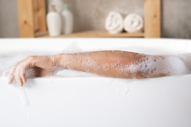 Braccio di giovane uomo rilassante nella vasca da bagno in porcellana bianca con schiuma sullo spazio della mensola con asciugamani e prodotti per la cura del corpo