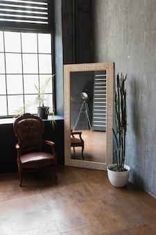 Poltrona con specchio vintage in interni in stile loft