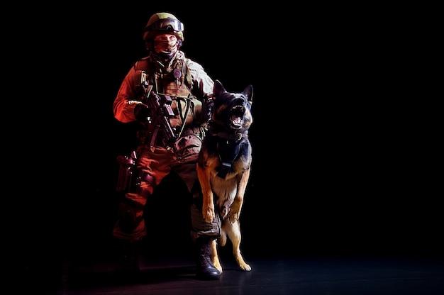 Un uomo armato in uniforme militare con una mitragliatrice trattiene un cane da servizio che abbaia. tecnica mista