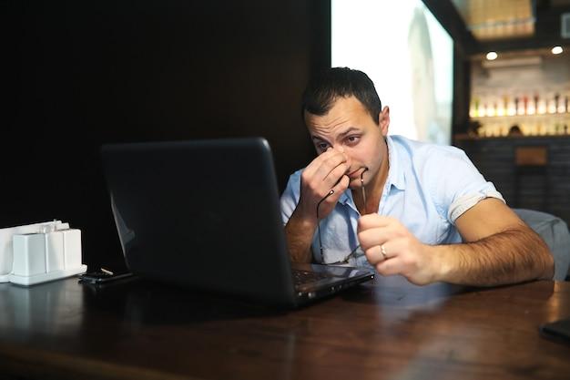 Bel uomo armeno che lavora dietro il laptop in un caffè